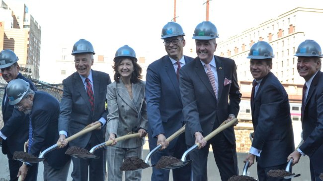 Several officials scoop dirt with shovels for the groundbreaking ceremony of The Hub