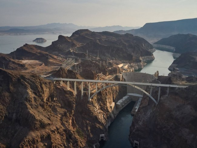 A vast mountain landscape with a bridge and a dam
