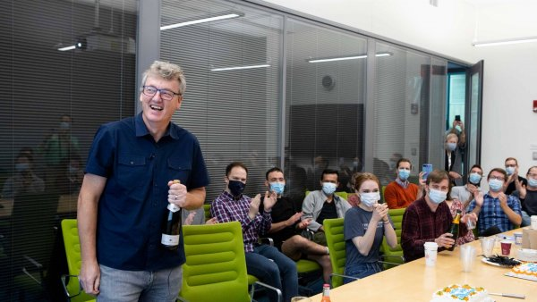 David MacMillan stands with a bottle of champagne in front of his lab group of students