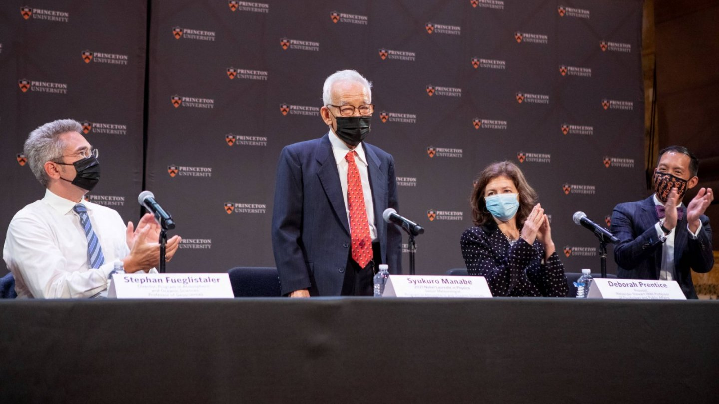 Syukuro Manabe stands for applause during a media conference